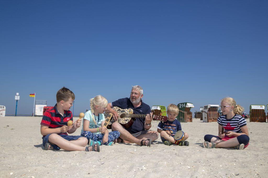 Kinder am Strand mit Gitarre