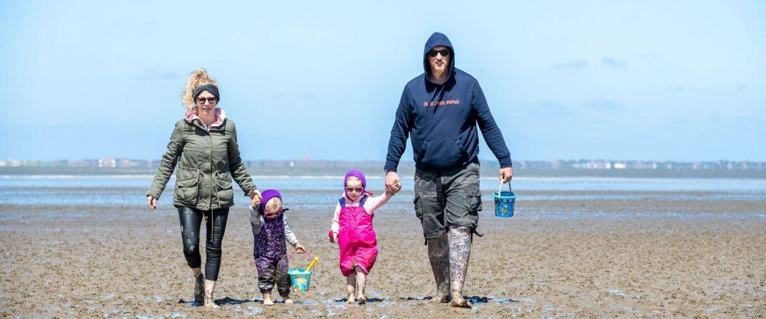Familie spaziert im Watt